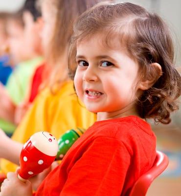 older preschooler girl holding musical instrument