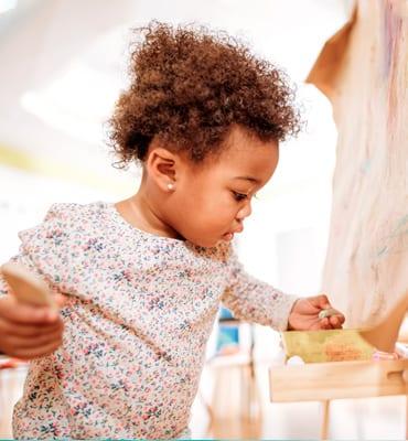 older toddler creating art at preschool