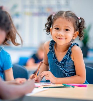 school age girl writing at preschool