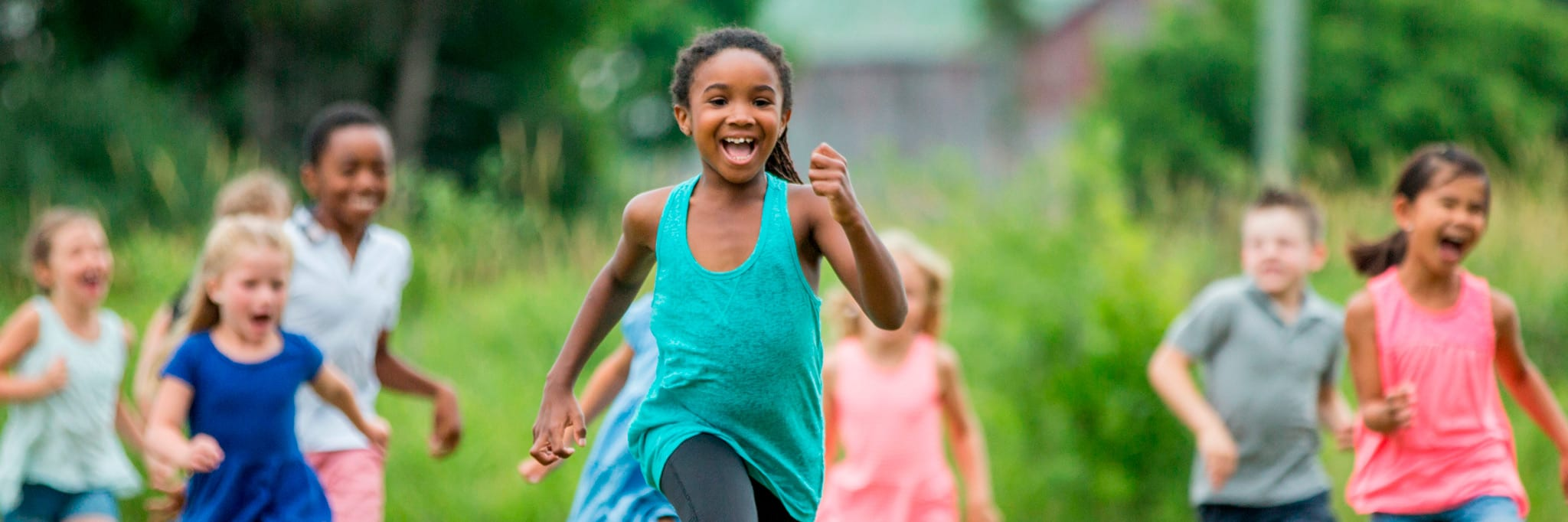 summer camp girl running in field with friends