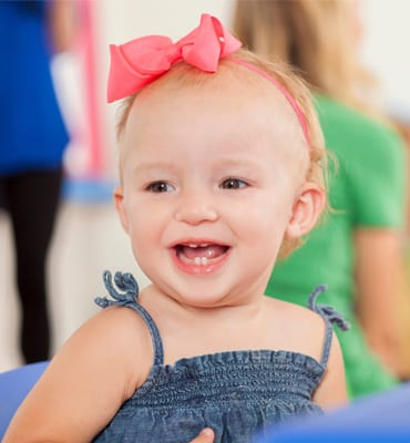 young toddlers program, girl with bow smiling at preschool